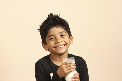 Young, Smiling Boy Holding a Cup of Milk